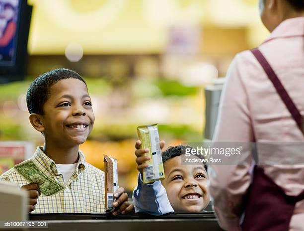 Two boys (4-9) paying for chocolates at checkout, smiling