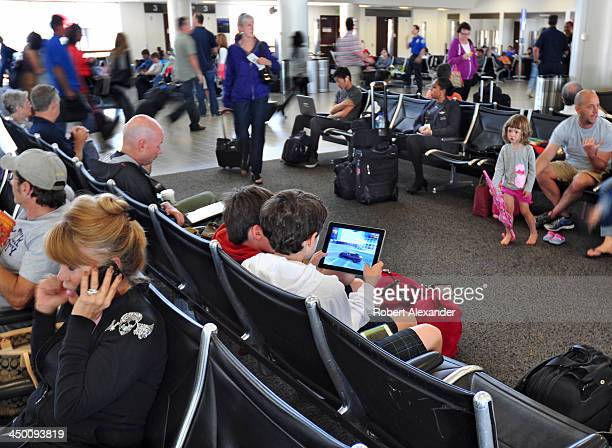 Two boys play a digital or video game on their tablet mobile device while waiting to board their plane at Los Angeles International Airport