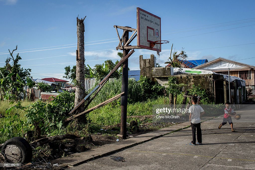 Two boys play basketball on April 19, 2014 in Palo, Leyte, Philippines. Basketball is the most popular sport in the Philippines. In the aftermath of Superstorm Yolanda that struck the coast on November 8, 2013 leaving more than 6000 dead and many more homeless, basketball hoops were some of the first things to be repaired and rebuilt amongst the rubble, showing the Filipino's resilience and intense love for the sport. Five months after the storm, basketball courts have re-emerged in large numbers across the damaged provinces using any available space and many being rebuilt from storm debris.