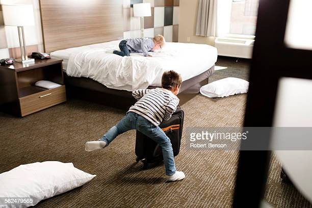 Two boys play in a motel room.