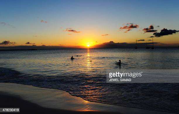 Two boys play on the water as sun sets in Bridgetown on March 12 2014 AFP PHOTO/Jewel Samad