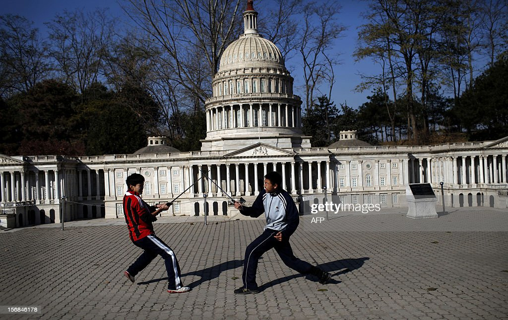 Two boys play sword in front of the mini replica of the United States Capitol in Beijing World Park, in the southwestern suburb of Beijing on November 23, 2012. Beijing World Park, with a collection of mini replicas of famous architectures from all over the wolrd, attempts to give visitors a chance to see the world without having to leave Beijing. CHINA OUT AFP PHOTO