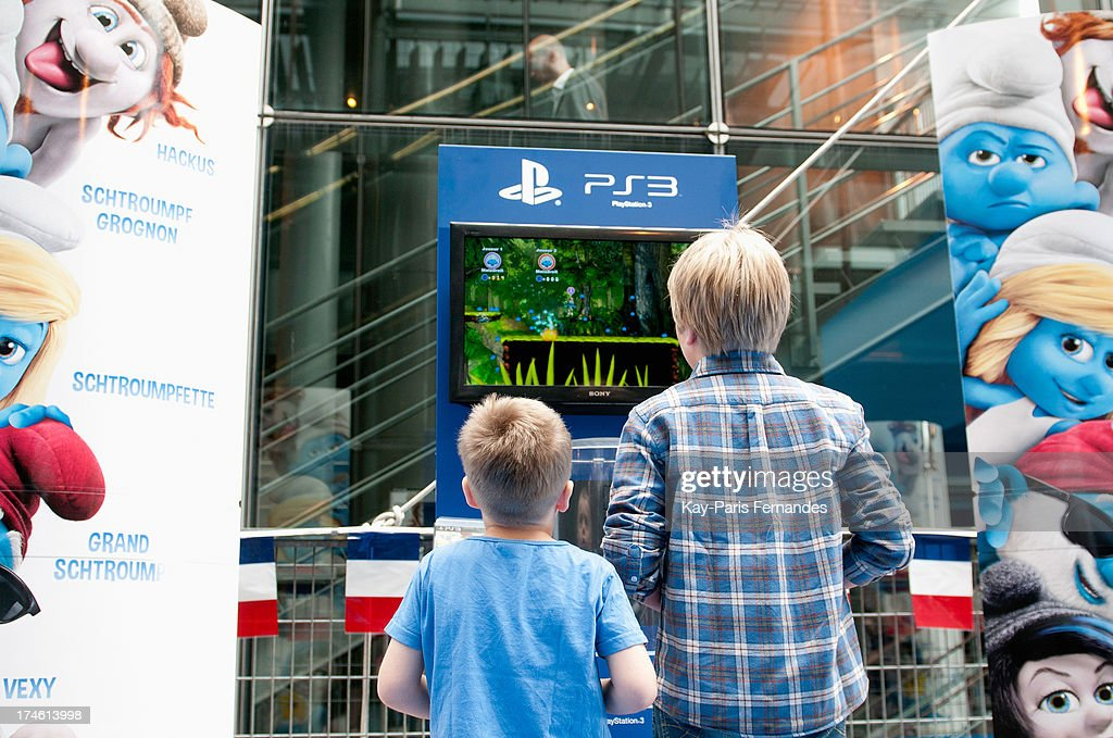 Two boys play the Smurfs video game on a game console at the 'Smurfs 2' Paris Premiere at UGC Cine Cite Bercy on July 28, 2013 in Paris, France.
