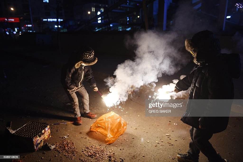 Two boys play with fireworks on a street in Beijing on February 7, 2016, the eve of the Lunar New Year. China marks the beginning of the Lunar New Year, the Year of the Monkey, on February 8. AFP PHOTO / GREG BAKER / AFP / GREG BAKER