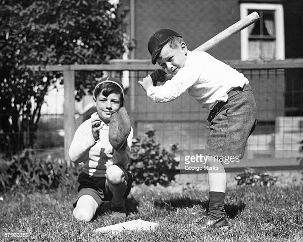 Two boys (6-7) playing baseball in garden, (B&W)