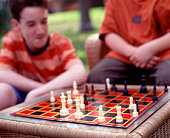 Two boys playing chess outside