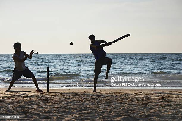 Two boys playing cricket on beach, Kudle Beach, Gokarna, India