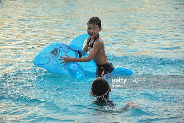 Two boys playing dolphin balloon in the pool