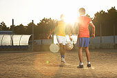 Two boys (11-13) playing football, lens flare