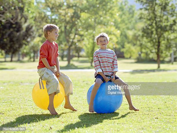 Two boys (8-10) playing on inflatable hoppers