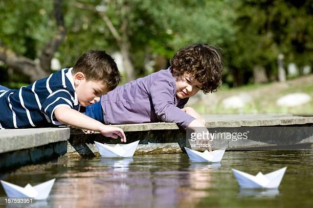 Zwei Jungen spielen mit Papier Boot