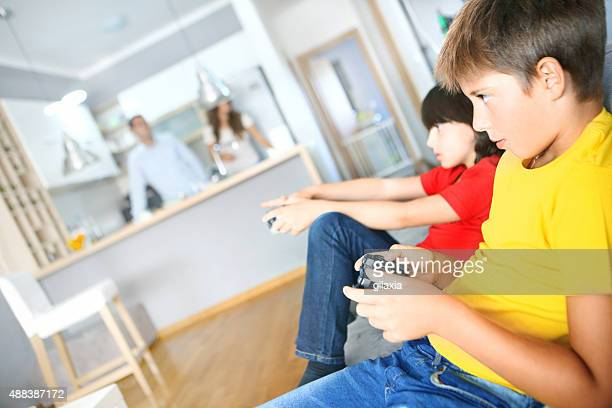 Two boys playing video games at home.
