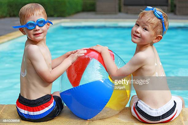 Deux garçons jouant avec un ballon de plage coloré sur la piscine