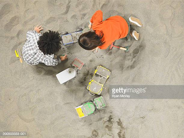 Two boys (5-7) playing with toy trucks in sandbox, overhead view