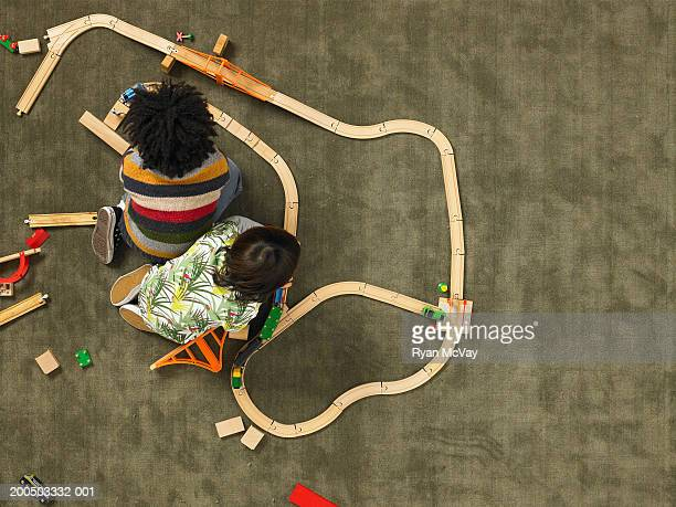 Two boys (5-7) playing with train set, overhead view