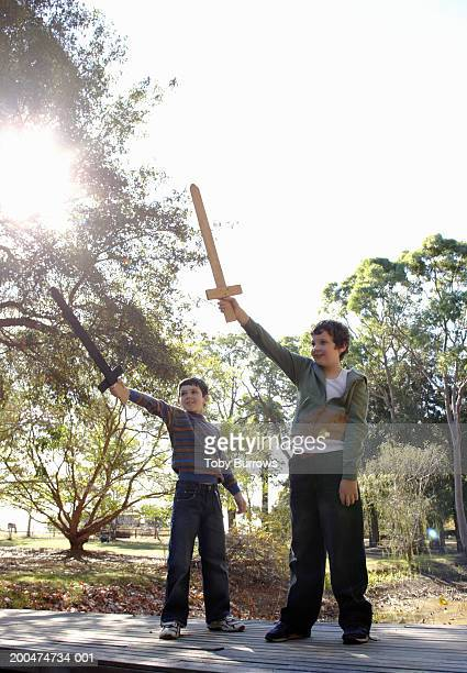 Two boys playing with wooden swords
