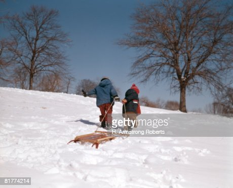 Two boys pulling sled up hill in snow. : Stock Photo