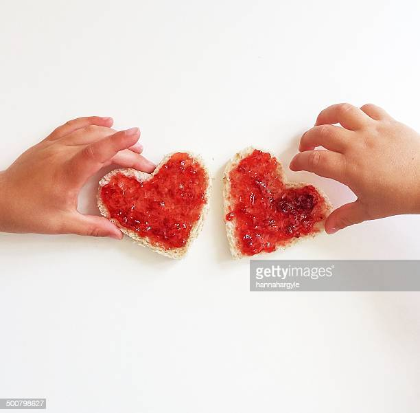 Two boys reaching for heart shaped slice of bread and jam