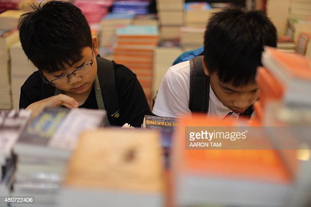 Two boys read near towers of books at Hong Kong's annual book fair on July 15 2015 The 26th edition of the fair showcased a record number of over 580...