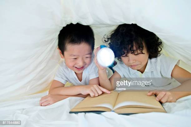 Two boys reading a book under the covers