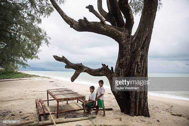 Two boys relax under a tree in a village inside the planned Dawei SEZ on August 3 2015 in Ngapitat MyanmarThe controversial multibillion dollar Dawei...