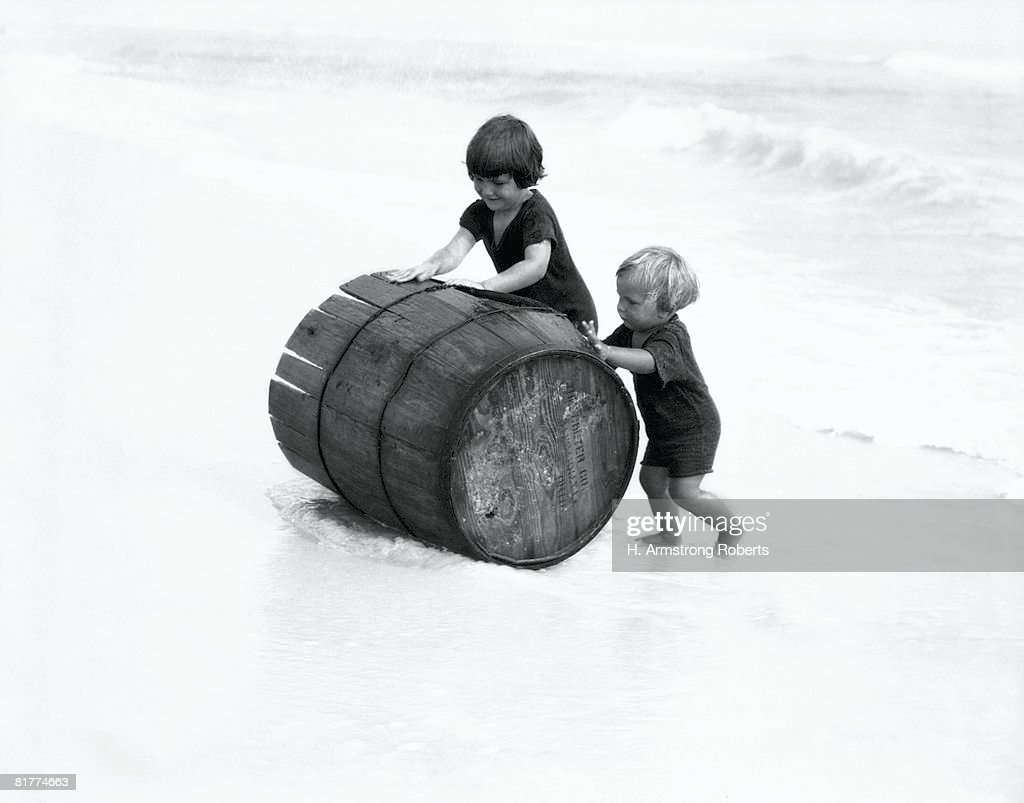 Two boys rolling broken barrel out of surf up onto sand beach, New Jersey. : Stock Photo