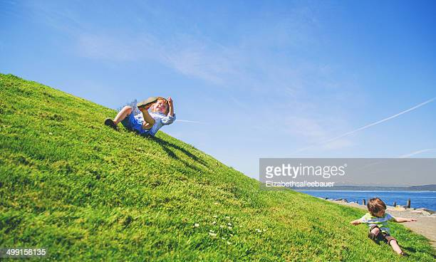 Two boys (2-3, 3-4)  rolling down grassy hill