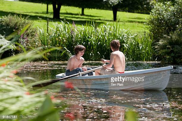 Two boys rowing a boat.