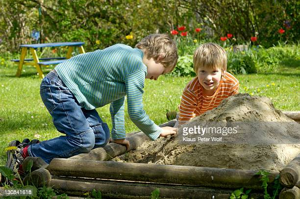 Two boys seven and nine year old playing in the sandbox