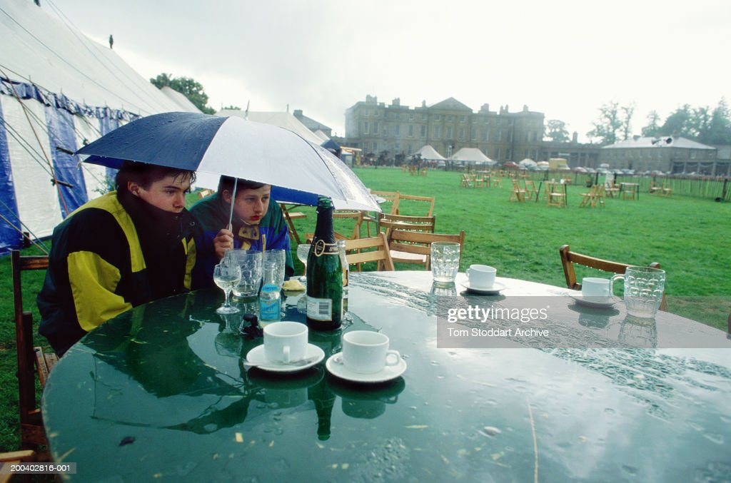 Two boys shelter under an umbrella during a rain downpour at the Rutland Show, which washed out the planned country events and competitions, UK, April 1990.