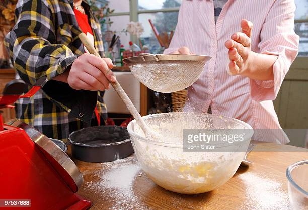 two boys sifting flour into cake mix
