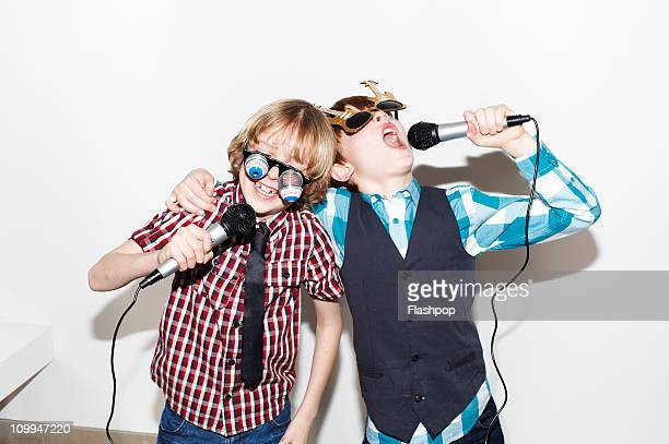 Two boys singing into microphones