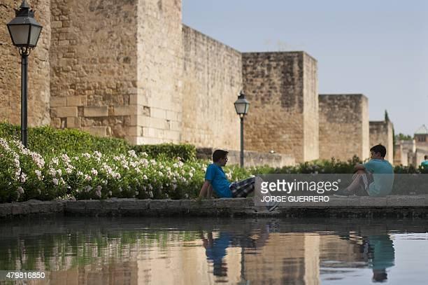 Two boys sit next the basin of a fountain in Cordoba on July 7 2015 In Spain started on July 1 2015 a new heatwave which will last for at least nine...
