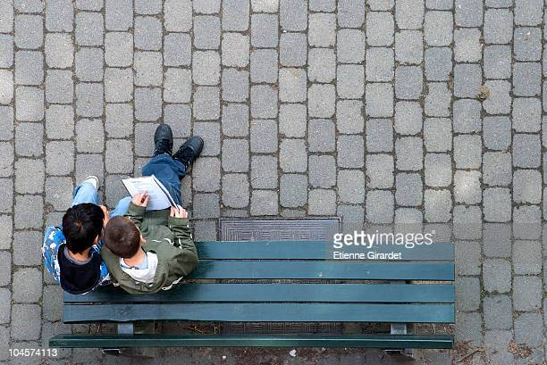 Two boys sitting on a park bench looking at a book