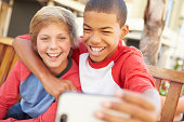 Two Boys Sitting On Bench In Mall Taking Selfie Smiling