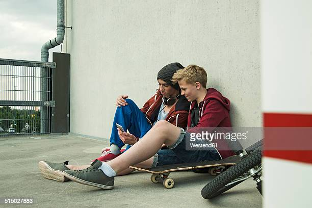 Two boys sitting on ground looking at cell phone