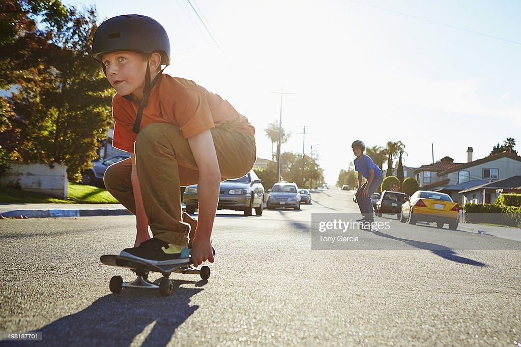 Two boys skateboarding on suburban road