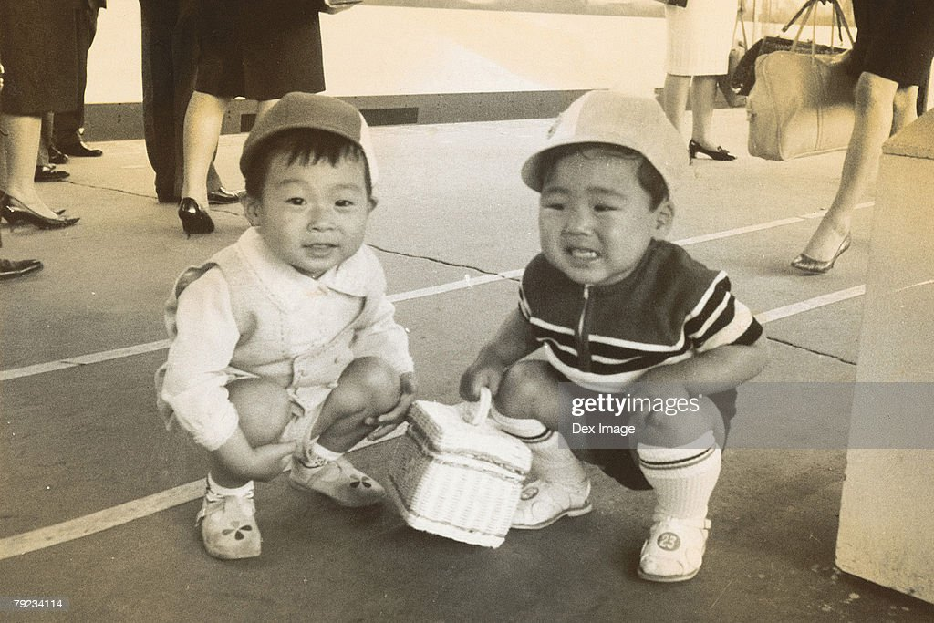 Two boys squatting in the middle of passage way : Stock Photo