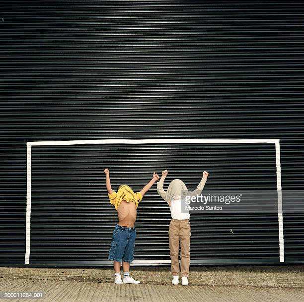 Two boys (6-8) standing by goal, shirts over heads