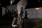 Two boys (12-13) standing in driveway, throwing eggs at house, night, rear view