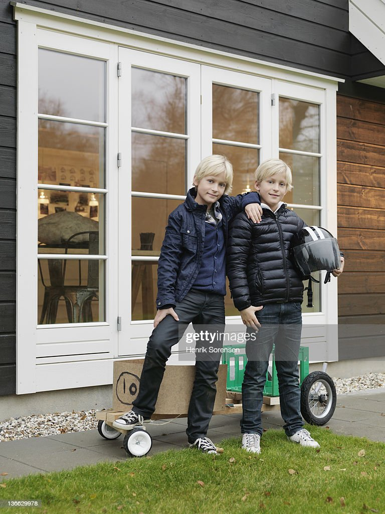 Two boys standing in front of house : Stock Photo