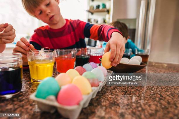 Two boys standing in the kitchen dying Easter eggs