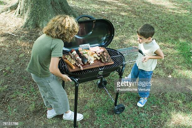 Two boys standing next to tray of grilled meat on barbecue