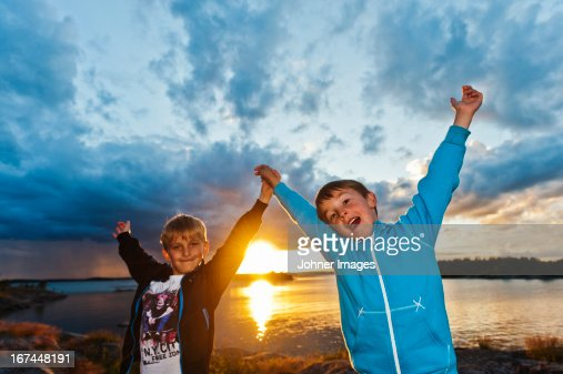 Two boys standing on beach at sunset : Stock Photo