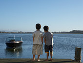 Two boys (6-7) standing on jetty, rear view
