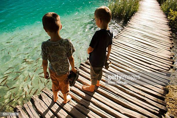 Two boys standing on timber boardwalk, Plitvice Lakes, Croatia