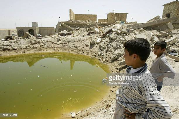 FALLUJAH IRAQ MAY 9 Two boys survey a building demolished during the monthlong siege May 9 2004 in Fallujah Iraq Residents continue their return to...