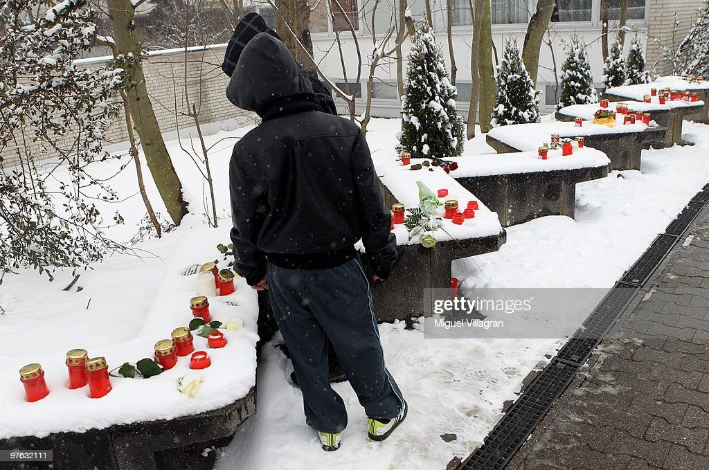 Two boys take a look at candles and flowers on a wall close to the Albertville School on March 11, 2010 in Winnenden, Germany. Tim Kretschmer opened fire on teachers and pupils at his former school a year ago on March 11, 2009, killing 15 and leaving many more injured. Kretschmer fled the scene and shot himself dead after being cornered by police.