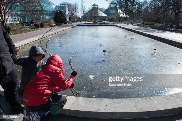Two boys test the ice of a frozen pool at the Brooklyn Botanic Garden during an arctic chill that brought frigid temperatures on February 14 2016 in...