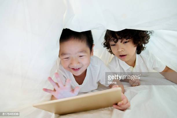 Two boys using digital tablet under the covers
